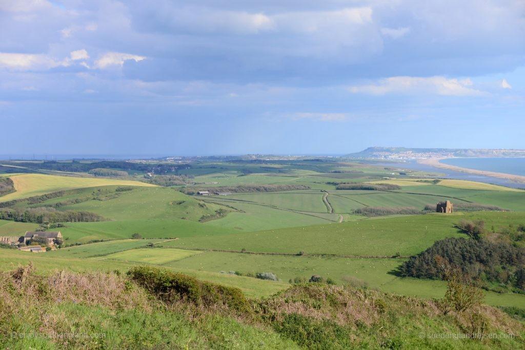 Ein Blick zurück: Links im Tal Abbotsbury, auf dem Hügel in der Mitte St. Catherines Chapel und rechts Chessil Beach an der Jurassic Coast