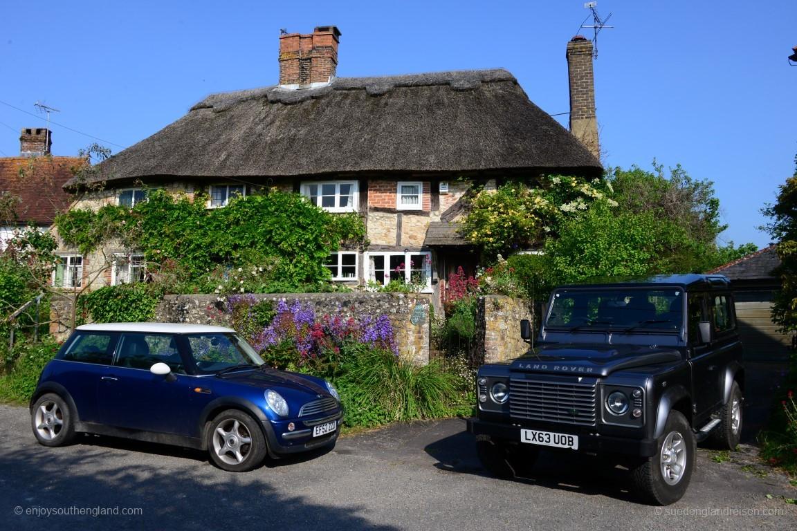 Klassischer geht es kaum: Ein traditionelles südengliches thatched Haus in Amberley mit zwei (ursprünglich) britischen Autos davor!