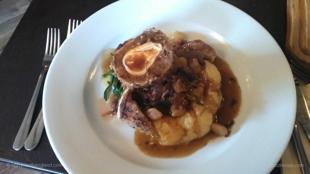 In der Pfanne gebratenes Schweinefilet an einem Scotch Egg mit Black Pudding an fein geschnittenem Schinken mit geschmorten Zwiebeln mit Schalotten-Chips und einer Rotweinsoße (Scotch Egg: Ei in einem Hackfleischmantel / Faschiertem; Black Pudding: Blutwurst / Blunzen)