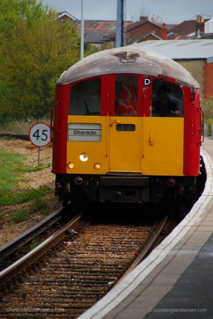 IOW Island Line - Ein Zug der Island Line in den charakteristischen klassische Farben der Londoner U-Bahn in rot mit gelber Front bei der Einfahrt in den Bahnhof von Shanklin.