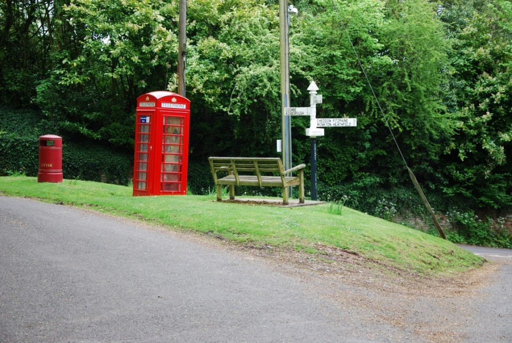 Eine ganz typische Wegkreuzung im Nirgendwo: Pillarbox, Telefonzelle, Bank und Wegweiser.